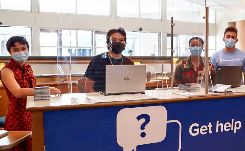 """student staff behind a desk with sneeze guard and signage that reads """"Get help here"""""""