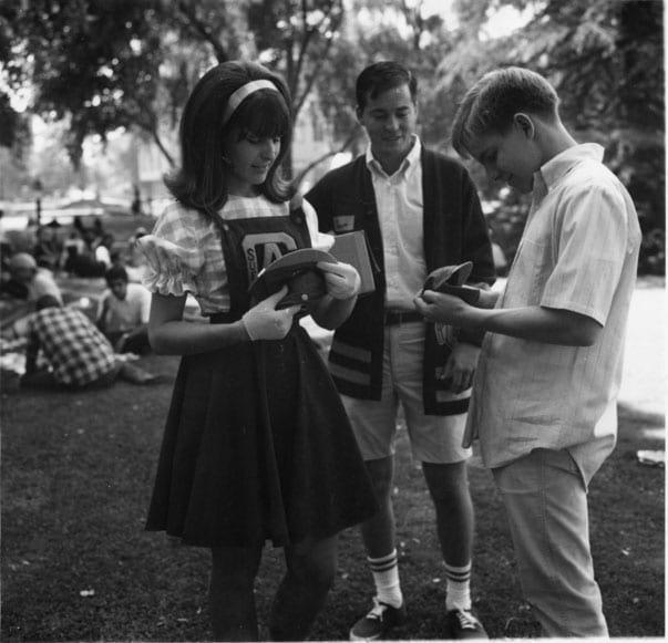 Orientation Week, student receives a freshman dink from a cheerleader, 1967 October.