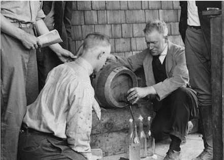 Viticulture professor William Cruess pouring from a wine barrel in about 1918