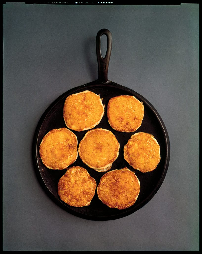 Seven pancakes in a round cast iron pan, undated.