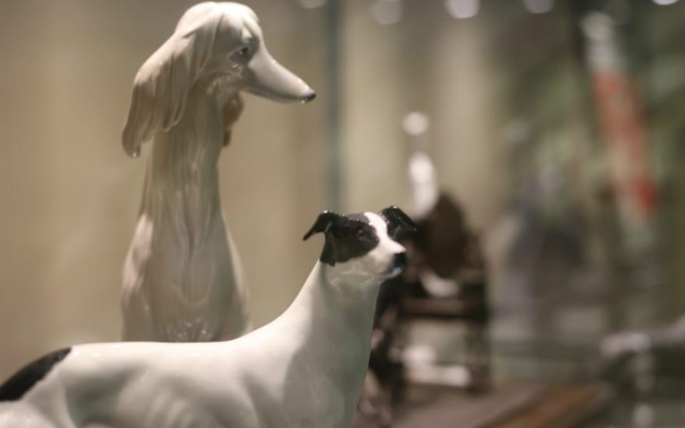 Two of the fine art pieces from the Sheila Grant Fleetfield Dog Museum and Library collection: In the foreground, a ceramic figurine of a black-and-white greyhound from the British studio Elite, and in the background, a white ceramic figurine of a sitting Afghan hound by the Spanish artist Lladró.