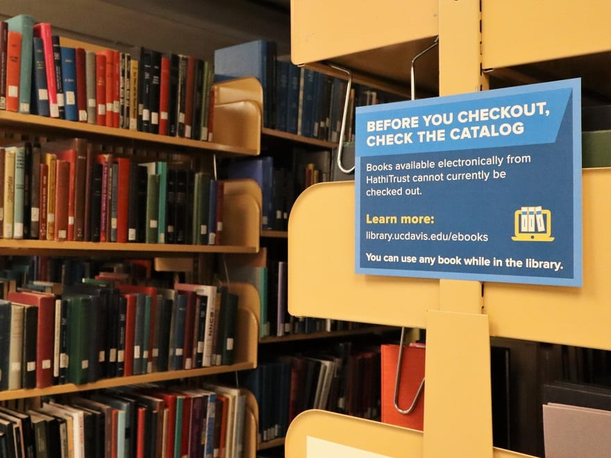 """Book stacks with sign that explains """"Books available electronically from HathiTrust cannot currently be checked out"""""""